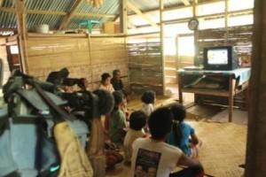 Anak dan orang tua di salah satu rumah di Desa Kamanggih menonton tv di siang hari
