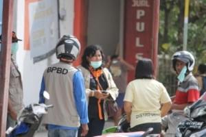 Tim Badan Bencana Sumba Timur sedang berbagi masker untuk masyarakat di sekitar Jembatan Payeti