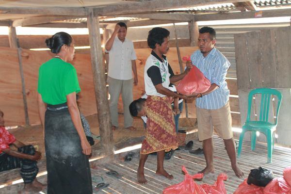 Relawan SaveSumba Umbu Nababan [Celana Pendek ] Berbagi Beras Sumbangan Dari Berbagai Pihak [ Foto : Heinrich Dengi ]